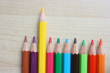 An odd yellow color pencil sticking up among others