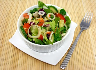 A mixed salad in a basket on bamboo place mat background