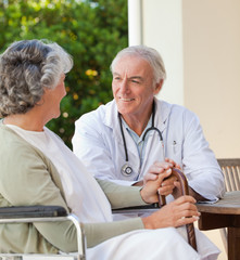 Senior doctor talking with his mature patient