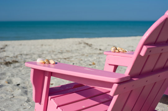 pink adirondack chair on beach