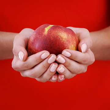 peach in woman hands