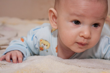 portrait of 4 months child playing on bed and looking at camera