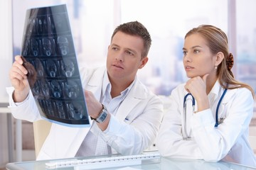 Two doctors studying x-ray image consulting