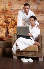 Portrait of bathrobe couple with laptop