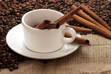 white coffee mug, beans and cinnamon sticks on sacking