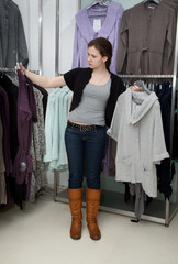 Девушка выбирает себе новую кофту в магазине одежды.