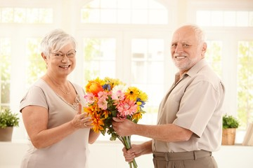 Portrait of happy senior couple with flower