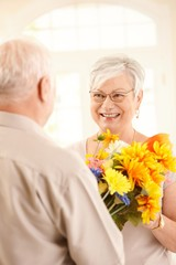 Happy elderly lady receiving flowers