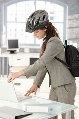 Young businesswoman leaving office by bike