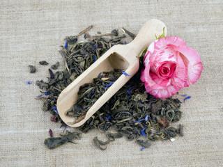 Green tea and wooden shovel on linen background