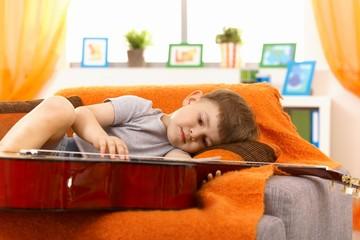 Little boy examining guitar on sofa