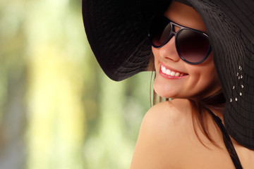summer teen girl cheerful in panama and  sunglasses over nature