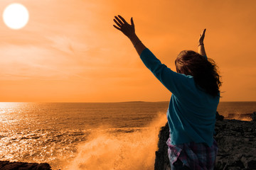 silhouette of lone woman facing a powerful  giant wave in sunshi
