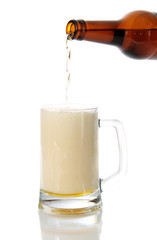 Beer flows from a bottle in a glass.