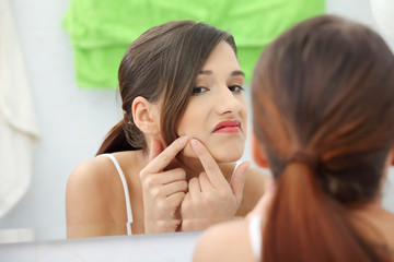 Young teenage woman with pimple
