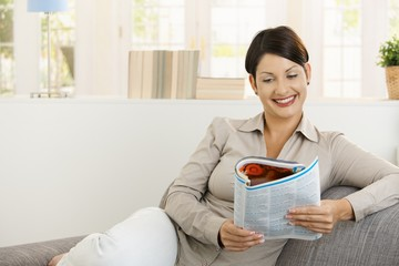 Happy woman reading newspaper on sofa