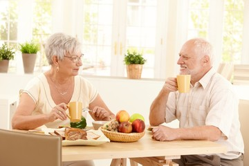 Happy elderly couple having breakfast