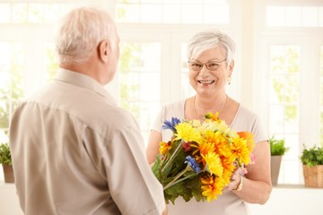 Happy elderly woman getting flowers