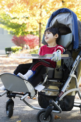 Disabled boy with cerebral palsy in medical stroller  at park