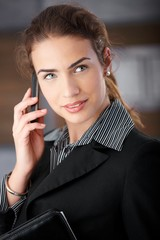Pretty businesswoman talking on mobile smiling