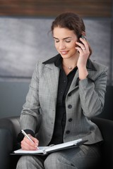 Smiling secretary on phone writing notes