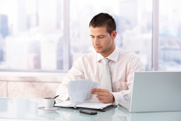 Young businessman working in bright office