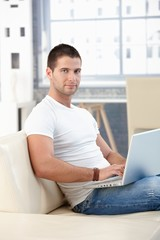 Sporty man browsing internet at home