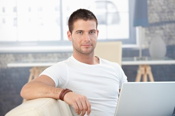 Portrait of handsome man with laptop