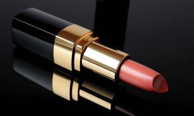 Luxury pink lipstick on black background. make-up