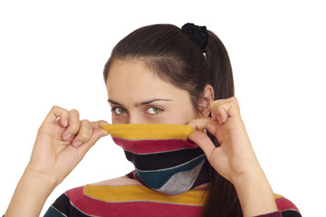 Attractive green-eyed woman pulling turtleneck sweater over her