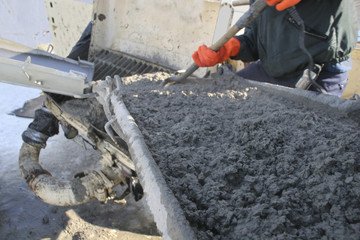 Construction worker pouring cement into pump