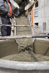 Truck operator pouring cement into crane bucket