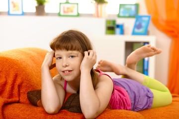 Little girl lying on sofa