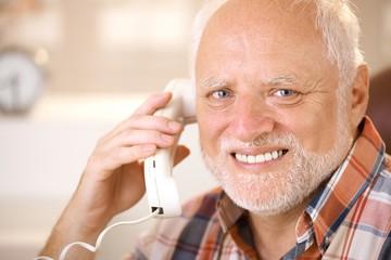 Portrait of smiling senior using landline phone