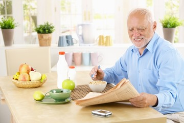 Older man reading newspaper in kitchen