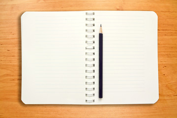 blank notebook with pancil on wooden table