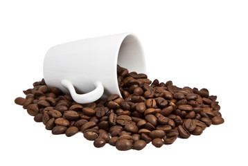 Coffee grains in a white cup and disseminated about a coffee pot