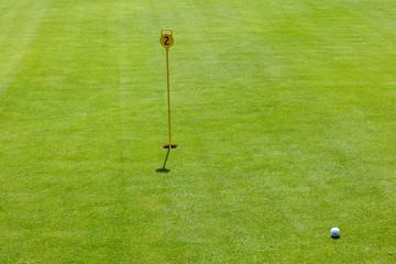 Golf Ball on fresh green near hole with flag pole