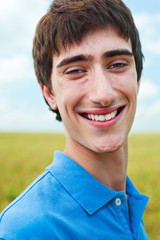 happy young man against blue sky