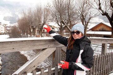 Girl with red gloves and snowball on a bridge