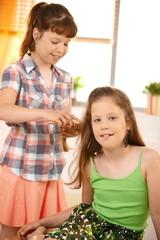 Cute girl combing friend's hair