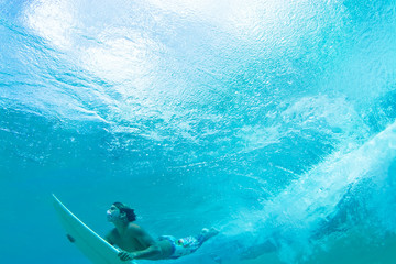 surfer water shot diving under wave white surfboard text