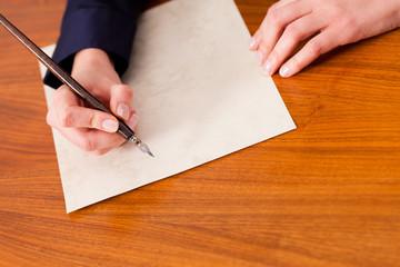 Frau schreibt einen Brief mit Feder und Tinte