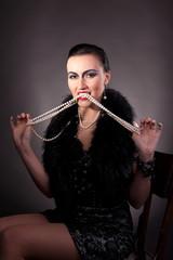 woman with vintage make-up take pearls in teeth