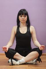 Темноволосая девушка медитирует после спортивных упражнений.