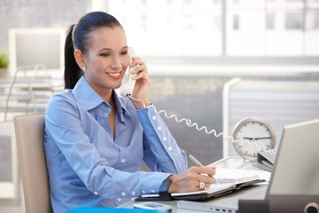 Happy office worker girl on phone call