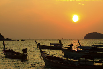Longtail boats on seashore at sunrise