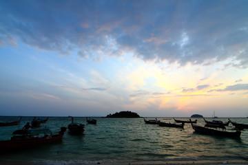 Longtail boats on seashore at sunrise
