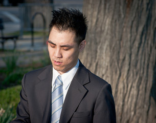 Asian Businessman Outside Looking Down Tree