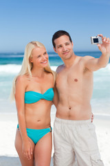 Couple taking a photo of themselves on the beach